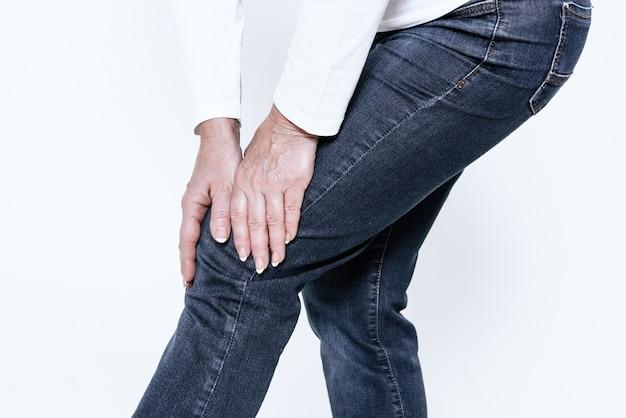 Une femme a mal au genou, elle fait un massage.
