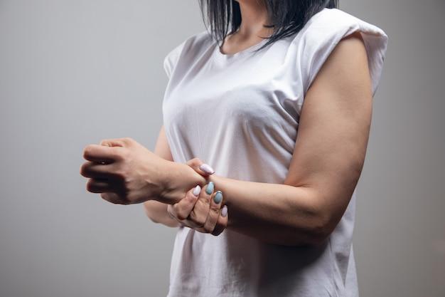 La femme a mal au poignet. douleur articulaire sur un mur gris