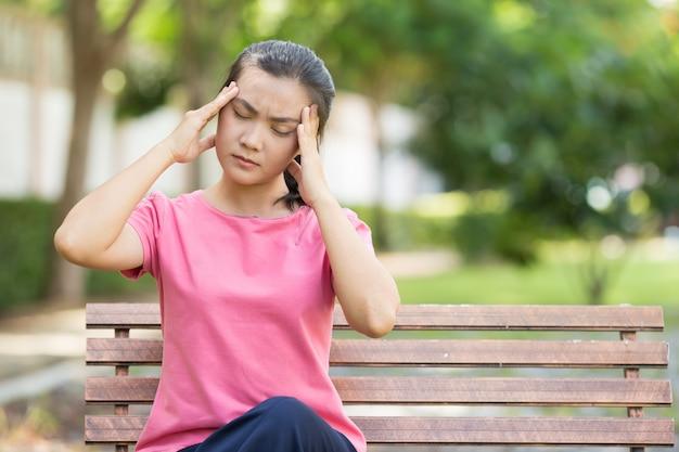 Femme a mal à la tête au jardin