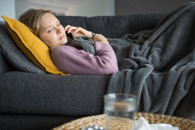 Femme malade allongée sur un canapé à la maison, appelant son mari au téléphone