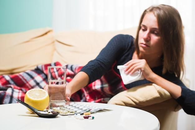 Femme malade allongée sur un canapé sous une couverture de laine, éternue et essuie le nez. pris froid