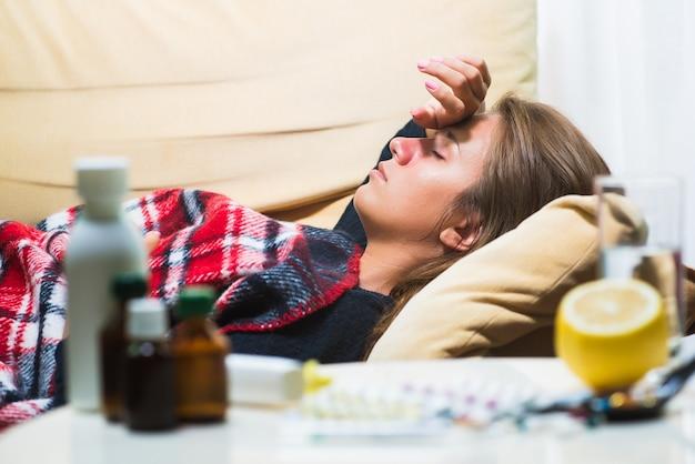 Femme malade allongée sur un canapé sous une couverture de laine