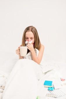 Femme malade assise dans son lit et tenant une tasse de thé
