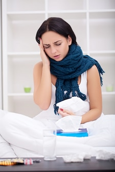 Une femme malade au lit avec un thermomètre fait de la fièvre à haute température