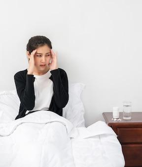 La femme malade avait mal à la tête et les mains touchaient sa tête sur le lit.
