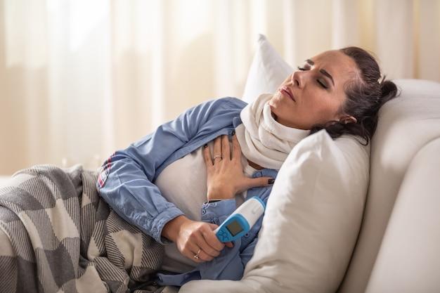 Femme malade ayant des problèmes de respiration et de toux tout en tenant un thermomètre frontal et en s'allongeant sur un canapé.