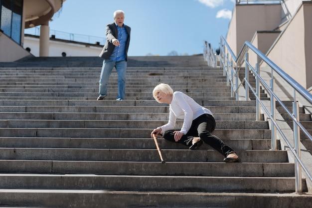 Femme malade bouleversée effrayée tombant dans les escaliers et exposant des crampes alors qu'un homme âgé se dépêchait de lui