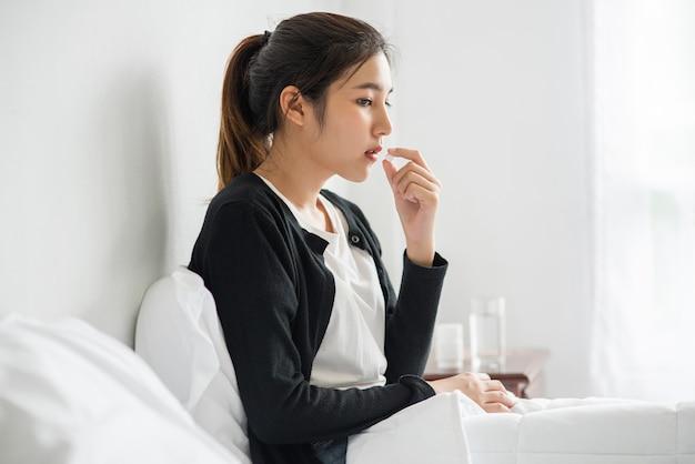 Une femme malade sur le canapé et sur le point de prendre des antibiotiques.