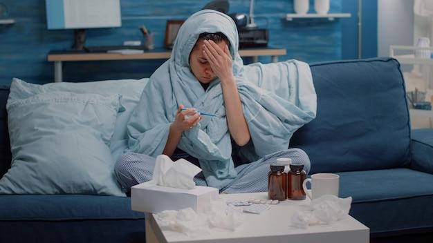 Femme malade couvrant avec une couverture et regardant un thermomètre