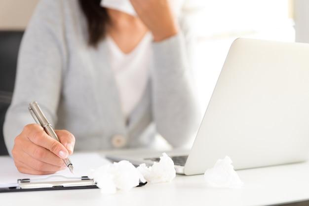Une femme malade dans le bureau, tenant à la main des tissus et éternuant dans un tissu blanc.