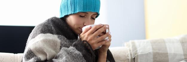 Femme malade, dans, chapeau, sous couverture, tient, tasse, médecine