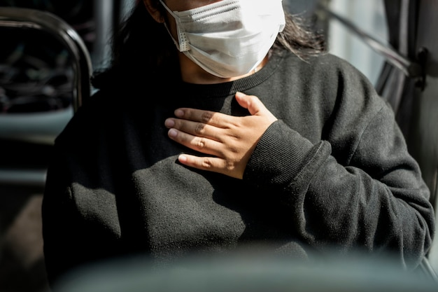 Femme malade dans un masque ayant des difficultés à respirer pendant la pandémie de coronavirus