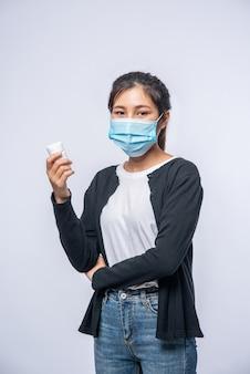 Une femme malade debout avec une bouteille de médicament