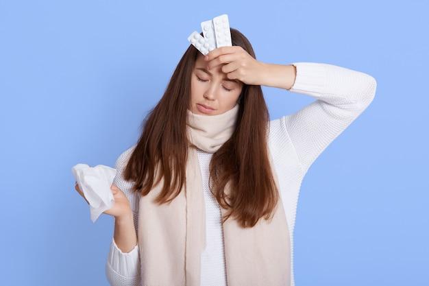 Femme malade déprimée bouleversée en écharpe chaude et pull décontracté, tenant une serviette et des pilules, fronçant les sourcils avec une expression misérable mécontente, isolée sur un mur bleu, garde les yeux fermés.