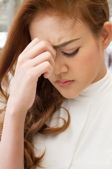 Une femme malade et déprimée souffre de maux de tête ou de dépression