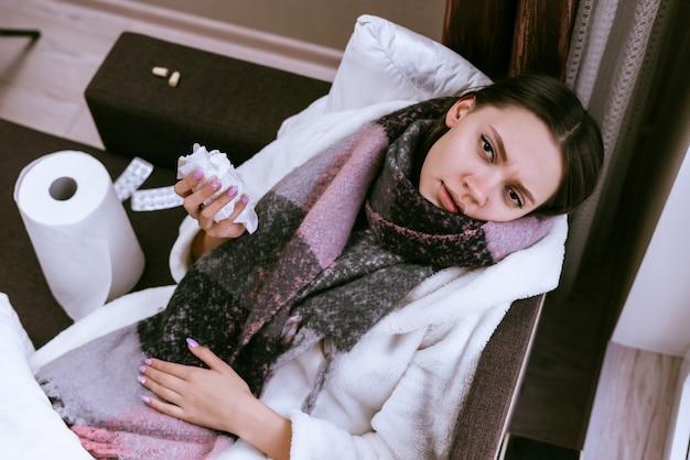 Une femme malade avec une écharpe chaude se trouve sur le fond des drogues