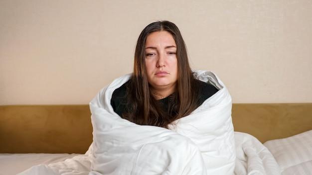 Une femme malade enveloppée d'une couette blanche douce est assise sur un grand lit dans la chambre