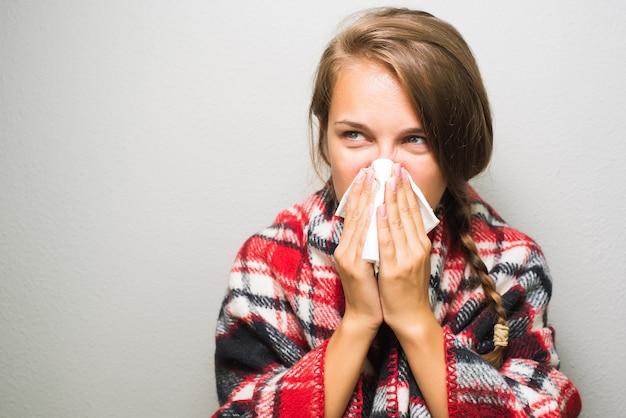 Femme malade en essuyant un nez