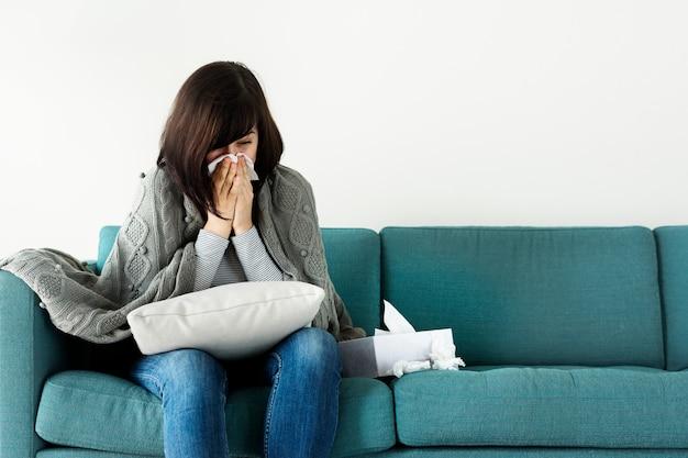 Femme malade en éternuant sur le canapé