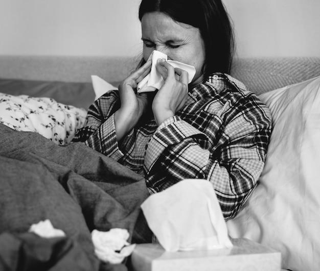 Femme malade éternue au lit