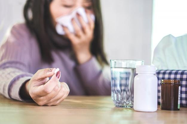 Femme malade éternue et prend des médicaments