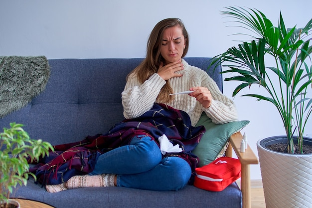 Femme malade avec forte fièvre et mal de gorge