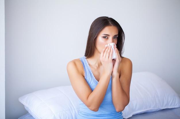 Femme malade et grippe. femme attrapée froide. éternuement dans le tissu