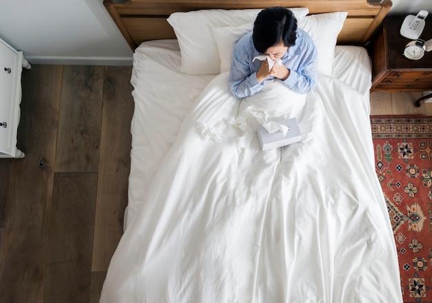 Femme malade sur le lit se moucher