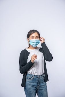 Une femme malade avec un mal de tête portait un masque et posa une main sur sa tête.