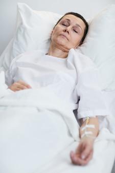 Femme malade mature allongée sur le lit à l'hôpital
