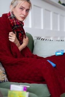 Femme malade avec un mauvais pressentiment enveloppée dans une couverture et souffrante.