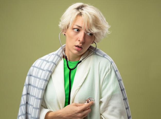 Femme malade en mauvaise santé avec les cheveux courts enveloppés dans une couverture se sentir mal avec un stéthoscope à l'écoute de son rythme cardiaque debout sur un mur léger