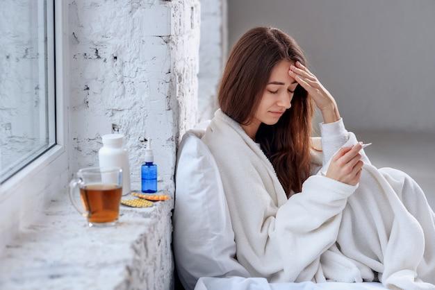 Femme malade avec maux de tête, maux de gorge et fièvre couverte d'une couverture se sentant malade