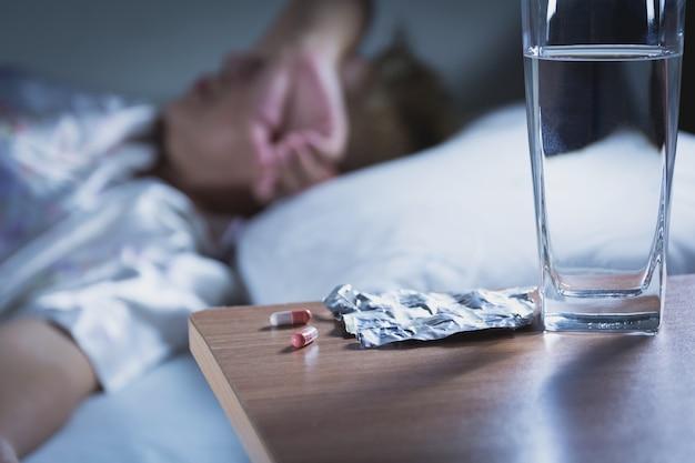 Une femme malade prend une pilule et boit de l'eau avant de dormir pour se reposer.