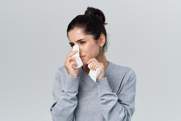 Une femme malade s'essuie le visage avec un mouchoir insatisfaction des problèmes de santé