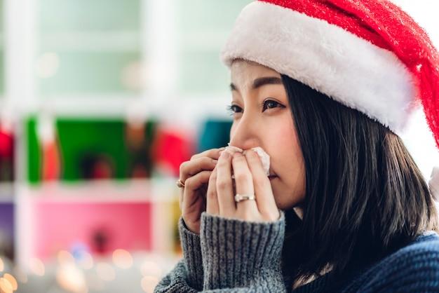 Femme malade se moucher le nez avec un mouchoir en papier et éternuer tout en ayant froid