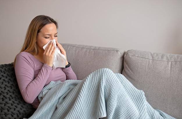 Femme malade, soufflant nez