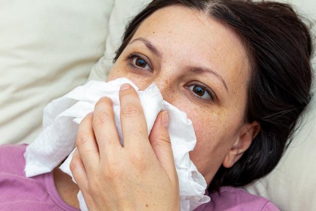 Une femme malade souffre de la grippe virale au lit, se mouche dans un mouchoir jetable