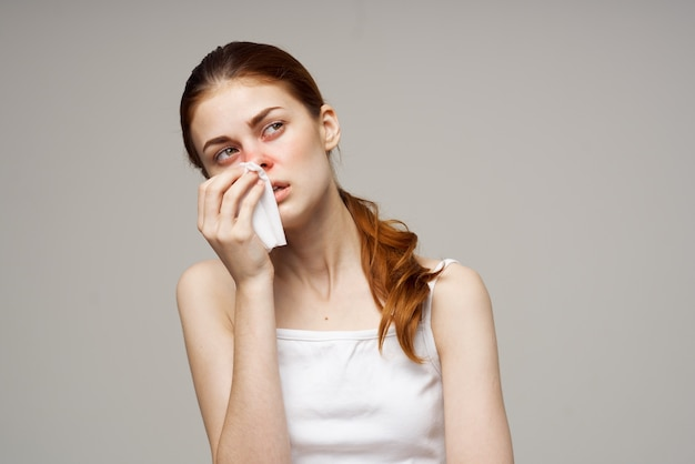 Femme malade en t-shirt blanc avec une écharpe fond isolé