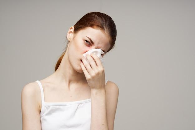 Femme malade en t-shirt blanc avec un fond clair d'écharpe