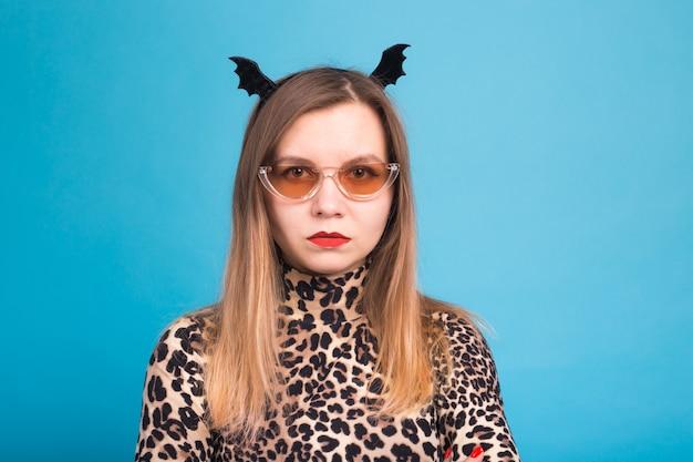 La femme maléfique avec une chauve-souris à la taille sur la tête. déguisement pour halloween sur mur bleu