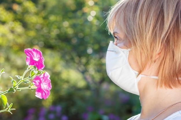 Femme malheureuse dans un masque de protection tenant un bouquet de fleurs sauvages et essayant de lutter contre les allergies au pollen. femme protégeant son nez des allergènes. notion d'allergie.