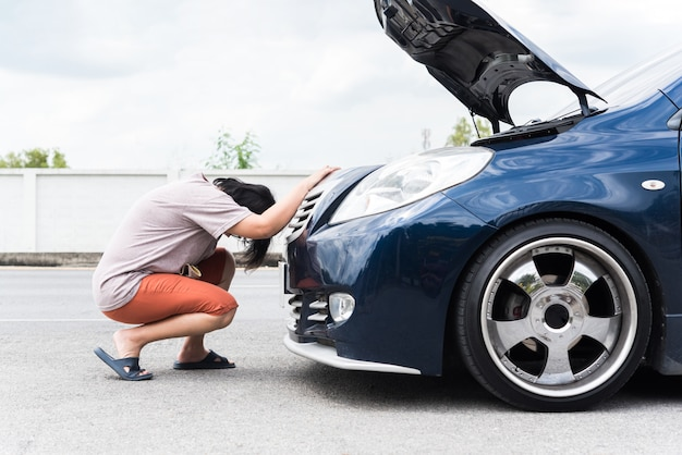 Femme malheureuse et lugubre d'un problème de moteur de voiture