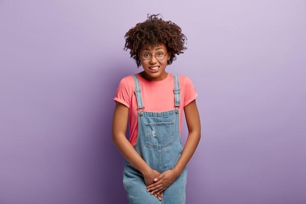 Une femme malheureuse à la peau foncée tient entrejambe, a besoin de toilettes, a une situation problématique, porte un t-shirt rose et un sarafan en denim, souffre de cystite, isolée sur un mur violet. les gens et l'urgence