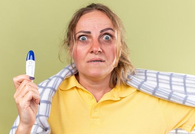 Femme malsaine enveloppée dans une couverture se sentant mal souffrant de la grippe et du rhume ayant de la fièvre tenant un thermomètre effrayé debout sur un mur vert