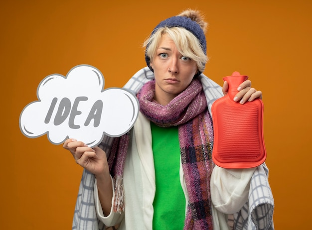 Femme malsaine malade aux cheveux courts dans une écharpe chaude et un chapeau enveloppé dans une couverture tenant une bouteille d'eau pour garder au chaud et signe de bulle de discours avec idée de mot malheureux et triste