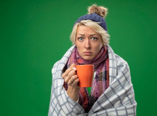 Femme malsaine malade aux cheveux courts dans une écharpe chaude et un chapeau se sentant mal enveloppé dans une couverture tenant une tasse de thé debout sur un mur vert