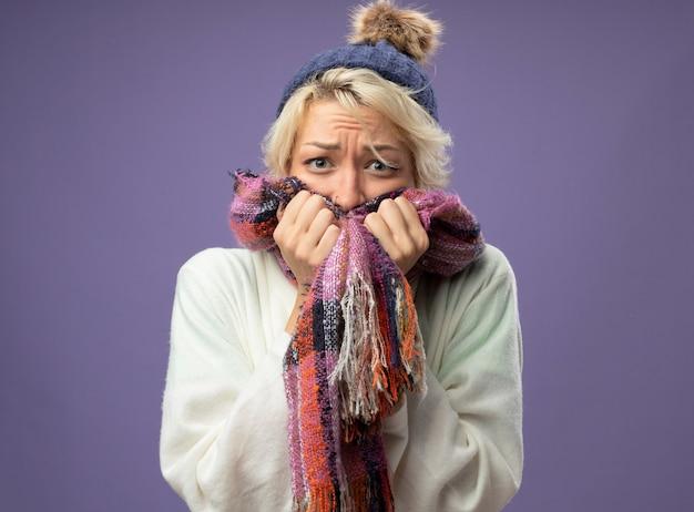 Femme malsaine malade aux cheveux courts en écharpe chaude et chapeau inquiet stressé et nerveux sur mur violet