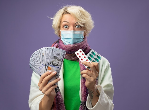 Femme malsaine malade aux cheveux courts en écharpe chaude et masque de protection faciale tenant de l'argent et des ampoules avec des pilules regardant la caméra en état de choc debout sur fond violet