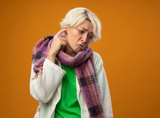 Femme malsaine malade aux cheveux courts en écharpe chaude se gratter l'oreille à côté d'être confus et triste debout sur le mur orange